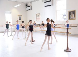 Group of girls performing ballet exercises at a barre in our studios at White Lodge