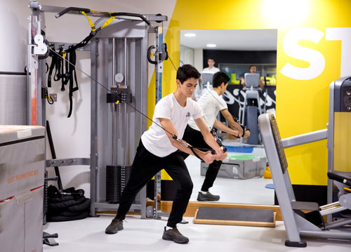 Student in the gym using a weights machine