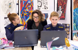 Two students at their laptops in an art class, with their teacher reading their screens over their shoulders.