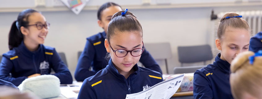 Student reading a worksheet in a classroom.