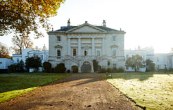 The exterior of White Lodge, a grand white building, in autumn sunlight.