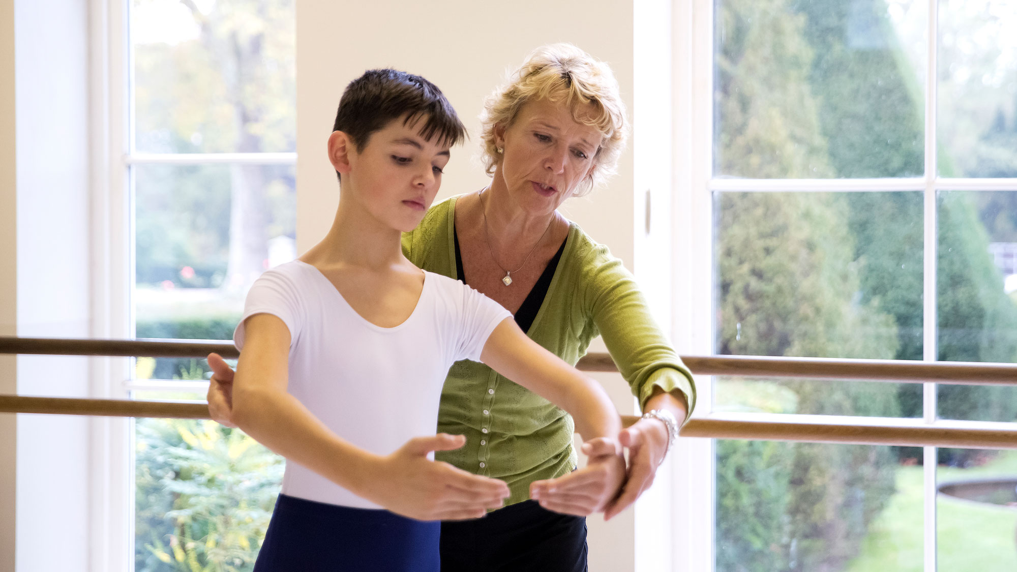 Ballet teachers behind a student doing centre work offering corrections