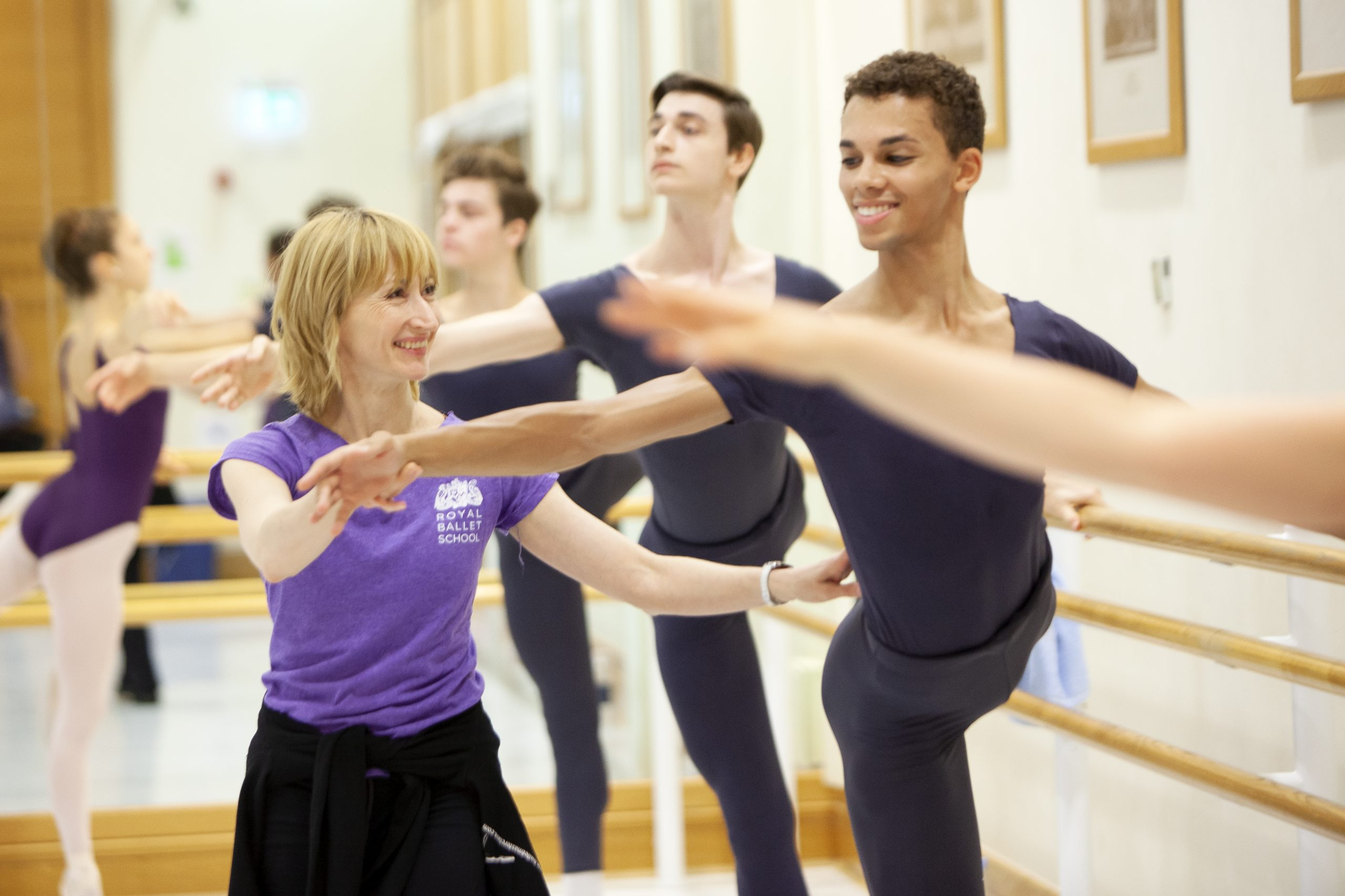 Ballet teacher helping a student at the barre